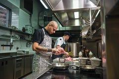 Enkel hoog - kwaliteit Geconcentreerde chef-kok die met tatoegeringen op zijn wapens verse rood vleesmier houden denkend over toe royalty-vrije stock afbeeldingen