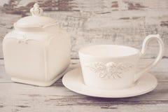 Enkel lantlig vit lerkärl, tömmer disk Ängel och ett porslin för stor kopp kaffe en främst skorrar med locket Träbakgrund som är  arkivfoto