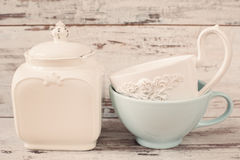 Enkel lantlig vit- och blåttlerkärl, tömmer disk Två stora bunkar och porslinkrus med locket Träbakgrund, sha royaltyfri fotografi