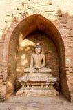 Enkel lerajord färgade Buddha med blomkrukan omgivet halvt Arkivfoton