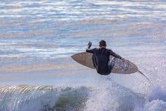 Enkel manlig surfare som är luftburen över våg arkivfoto
