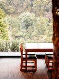 Enkel modern wood tabell och stol vid fönstret med för fotografering för bildbyråer