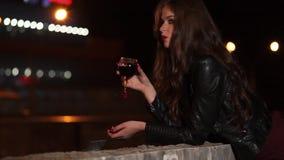 Enkel romantisk dam med rött vinexponeringsglas i en hand på den mörka nattgatan lager videofilmer