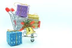 Enkel shoppingvagn med färgrika fyra gåvaaskar och den guld- klockan Royaltyfri Foto