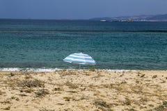 Enkel slags solskydd på stranden med turkoshavet Royaltyfri Bild