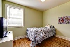 Enkel sovruminre med enkel säng och TV Arkivfoto