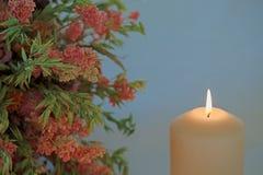 Enkel stearinljus och en bukett av torkade blommor royaltyfria bilder