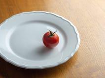 Enkel tomat med stammen på en vit platta på en trätabell royaltyfria bilder