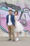 Enkel van het gehuwde koppelt houden hipster in huwelijkskleding en kostuum openlucht in stad die tegen kleurrijke graffitimuur p Royalty-vrije Stock Fotografie
