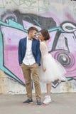 Enkel van het gehuwde koppelt houden hipster in huwelijkskleding en kostuum openlucht in stad die tegen kleurrijke graffitimuur p Royalty-vrije Stock Foto