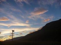 Enkel vindkraftgenerator i en bergdal med molnig himmel Royaltyfri Fotografi