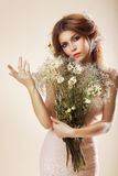 Enkelhet. Elegant behagfull kvinna med buketten av blommor som poserar i studio royaltyfri bild