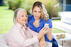 Enkelin, die Enkelin bei der Anwendung unterstützt Stockbilder