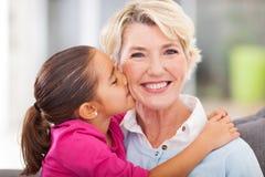 Enkelin, die Großmutter küsst Stockfoto