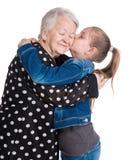 Enkelin, die ihre Großmutter küßt Stockfotografie