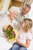 Enkelin, die ihrer Großmutter Blumen gibt Stockbilder