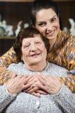 Enkelin, die ihrer Großmutter eine Umarmung gibt Stockfotos