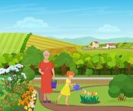 Enkelin, die um Blumen mit Großmutter im schönen Dorf in den Bergen wässert und sich kümmert Stockbilder