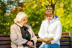 Enkelin liest sein älteres Großmutterbuch Lizenzfreie Stockfotos