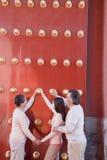 Enkelin mit den Großeltern, die nahe bei den traditionellen roten Türen und dem Händchenhalten stehen Stockfotografie