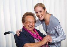 Enkelkind besucht Großmutter in einem Rollstuhl Stockfotos