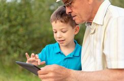 Enkelkind und Großvater, der draußen eine Tablette verwendet Stockfotos