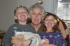 Enkelkinder, die Gesichter mit Großmutter malen Stockfotografie