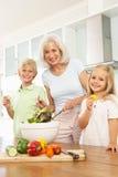 Enkelkinder, die Großmutter helfen, Salat zuzubereiten Stockfotografie