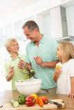 Enkelkinder, die Großvater helfen, Salat zuzubereiten Lizenzfreie Stockfotos