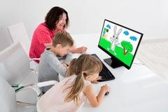 Enkelkinder, die zu Hause Farbauftrag auf dem Desktop verwenden Stockfoto