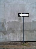 Enkelriktat tecken mot väggbakgrund Arkivfoton