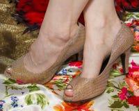 Enkels gekruiste teennagels en schoenen in goud stock foto