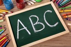 Enkelt alfabet för abc som är skriftligt på en svart tavla, läs- handstilbegrepp Royaltyfri Bild