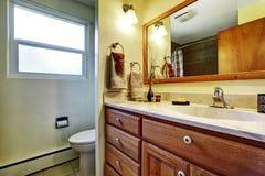 Enkelt badrum med bruna kabinetter, toaletten och ett fönster Arkivbilder