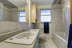 Enkelt badrum med det tegelplattagolvet och fönstret Royaltyfria Bilder