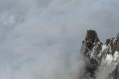 Enkelt bergmaximum som dyker upp från den tjocka molnräkningen Arkivfoto