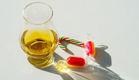 Enkelt exponeringsglas för maltwhisky med godisrottingen, symbolet av Christm royaltyfri fotografi