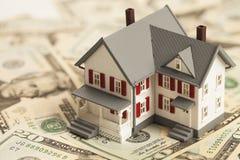 Enkelt familjhus på högen av pengar Arkivfoto