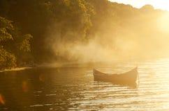 Enkelt fartyg i sjön på solnedgången Fotografering för Bildbyråer