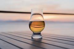 Enkelt gammalmodigt whiskyexponeringsglas vid havet Arkivfoton