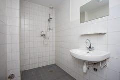 Enkelt gammalt rent badrum med den vit belade med tegel golvvasken och dusch royaltyfria bilder