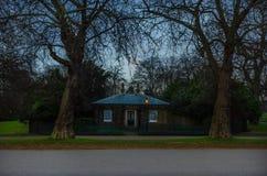 Enkelt hus mellan två stora träd Arkivbilder