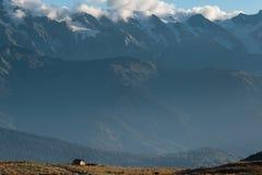 Enkelt hus på en bakgrund av berg Arkivbild