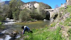 Enkelt kvinnasammanträde vid en flod i en Pyrenean by, Frankrike arkivfilmer