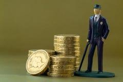 Enkelt miniatyrmodell och engelska för affärsman ett pund mynt Royaltyfri Foto
