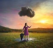 Enkelt moln som regnar på en kvinna arkivbild