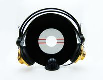 Enkelt rekord för vinyl med guld- hörlurar på vit bakgrund arkivbild