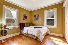 Enkelt sovrum med enkel säng i färgrik sängkläder Arkivbilder