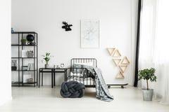 Enkelt sovrum med svart säng Arkivbild