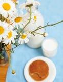Enkelt stilfullt träkök med flaskan av mjölkar, och exponeringsglas på tabellen, sommar blommar kamomill, sund matmorgon Royaltyfri Fotografi